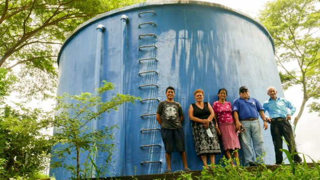 Members of the Cangrejera Drinking Water Association in the Desvío de Amayo village, La Libertad municipality in central El Salvador, stand at the foot of the tank from which water flows by gravity to the nine villages that benefit from this community project. There are an estimated 2,500 rural water boards in the country, which provide service to 1.6 million people. CREDIT: Edgardo Ayala/IPS
