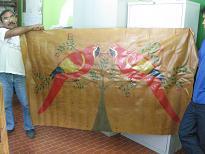 Nenzinho holds up wall hanging made of latex fabric. Credit: Mario Osava/IPS