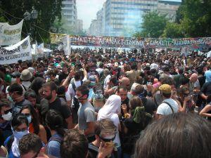 Protestors surround Greek parliament, many wearing masks against tear gas. Credit: Bego Astigarraga/IPS
