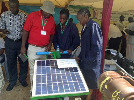 Emma Masibo (links) mit Lucy Bwire und ihrem Mentor Peter Wamalwa mit dem Prototypen ihres Solarmähers (Bild: Justus Wanzala/IPS).