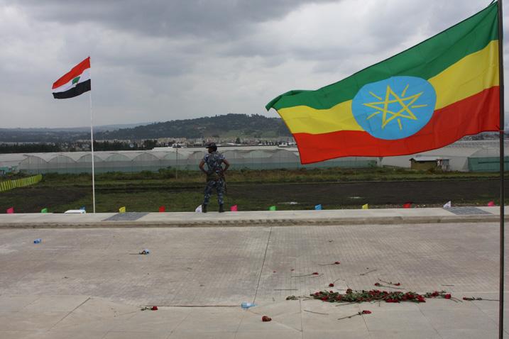 Ein Polizist zwischen den Flaggen der Verwaltungsregion Oromia (links) und der Demokratischen Bundesrepublik Äthiopien (Bild: James Jeffrey/IPS)