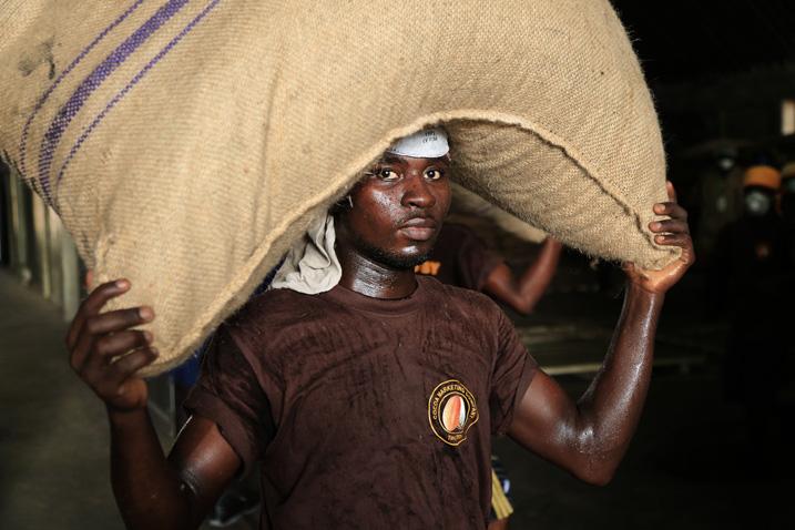 Ein Arbeiter schleppt Kakaosäcke im Trockenhafen von Accra (Bild: Jose Carlos Alexandre/Shutterstock.com)