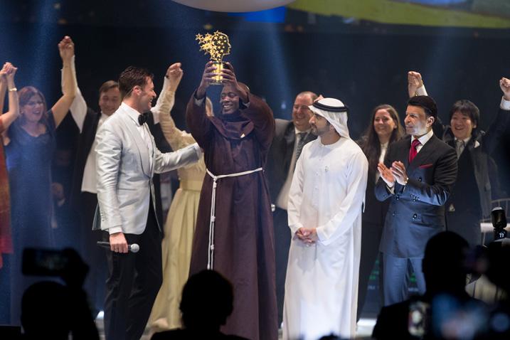 """Verleihung des """"Global Teacher Prize"""" in Dubai. Im Vordergrund von links nach rechts: Hugh Jackman, Peter Tabichi, Kronprinz Sheikh Hamdan bin Mohammed bin Rashid Al Maktoum und Sunny Varkey, Gründer der Varkey Foundation (Verwertung honorarfrei, Bildrechte: Varkey Foundation)"""