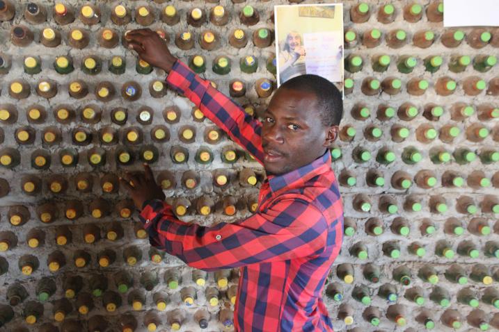 David Monday erklärt das Prinzip eines aus Plastikflaschen errichteten Hauses (Bild: Wambi Michael/IPS).