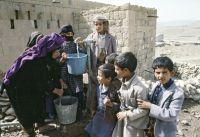 Children help an old woman fill her containers with water from a community pump in Dobra Khira near Sanaa, Yemen. / Credit:UN Photo/Ian Steele